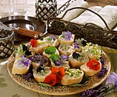 Baguette appetisers with herb leaves and flowers