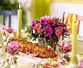Laid table with Easter plait and spring flowers
