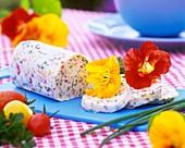 Kräuterbutter, dekoriert mit Blüten von Kapuzinerkresse