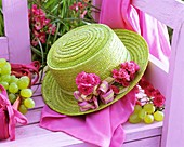 Green straw hat with roses on pink bench, grapes