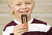 Boy eating Ischokladkaka (Chocolate biscuit cake, Sweden)