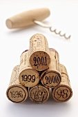 Wine corks from various vintages with corkscrew