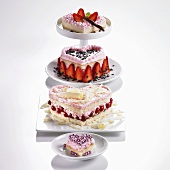 Four heart-shaped sponge cakes with redcurrants or strawberries & cream