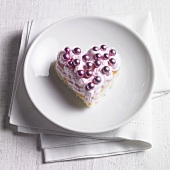 Heart-shaped sponge cake with strawberry cream and dragees