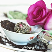 Tea leaves, flowering tea, tea infuser and pink roses