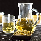 Chamomile tea in glass jug and glass cup, chamomile flowers