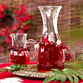 Cranberry juice in carafe and glass jug (Christmas)