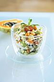 Crab salad with exotic fruit in a glass