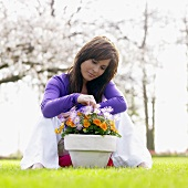 Woman on grass with pot of anemones and pansies