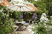 Sitzgruppe mit Sonnenschirm im sommerlichen Garten