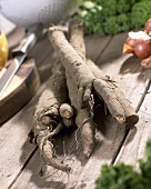 Greater burdock roots (Arctium lappa) on wooden table