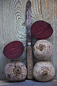 Whole and halved beetroot with old knife against wooden wall