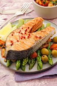 Salmon steak on green asparagus, olives and tomatoes