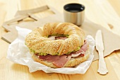 Bagel filled with ham and avocado paste
