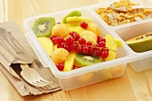 Fruit salad, muesli and half a papaya in a plastic box