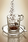 Coffee granules falling into glass cup