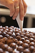 Decorating chocolates with a piping bag