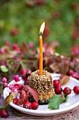 Cannele with candle and rose hips