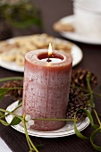Candle with mistletoe and pine cones
