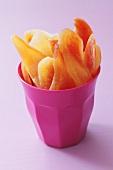 Dried papaya slices in pink beaker