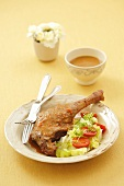 Roast goose leg with iceberg lettuce and tomato