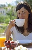 Junge Frau trinkt Tee am Frühstückstisch