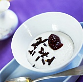 Vanilla cream with berry sauce and pieces of chocolate