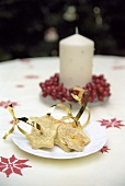 Star-shaped sesame biscuits and candle with winterberries