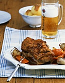Joint of suckling pig with crackling on vegetables cooked in beer
