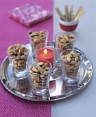 Salted almonds and candle on silver tray