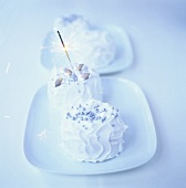 Small cakes with white icing and sparkler