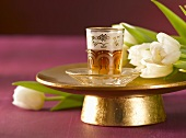 Tea in Middle Eastern tea glass on golden stand, tulips