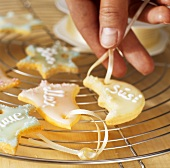 Putting ribbon hangers through holes in biscuits