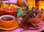 Cup of tea, candle glass, autumn leaves & Virginia creeper