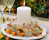 Clematis-Kranz mit Zieräpfeln und weisser Kerze