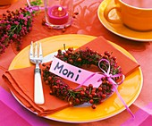 Place-setting with rose hip wreath and place card