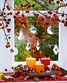 Zieräpfel, Glashänger und Kerzen am Fenster