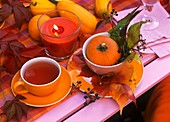 A cup of tea on a table with autumn decorations