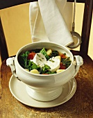 Kale and tomato stew with goat's cheese