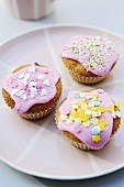 Three fairy cakes with pink icing and decorations