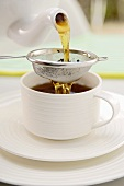 Pouring tea through a tea strainer