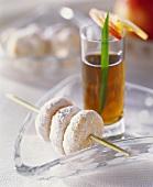 Marzipan cookies threaded on skewer, tea in background