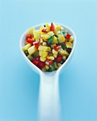 Mango salsa with sweetcorn kernels on spoon