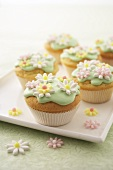 Muffins with green icing and sugar flowers on tray