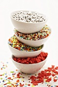 Four bowls of sprinkles (dragees, sugar hearts etc.)