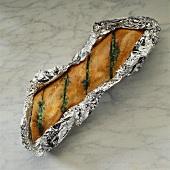 Grilled herb baguette in aluminium foil