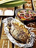 Fish with lemon slices cooked in aluminium foil