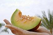 Hand holding a piece of Thai melon