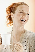 Red-headed woman holding a teacup (laughing)