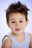 Kleiner Junge schleckt sich den Mund ab